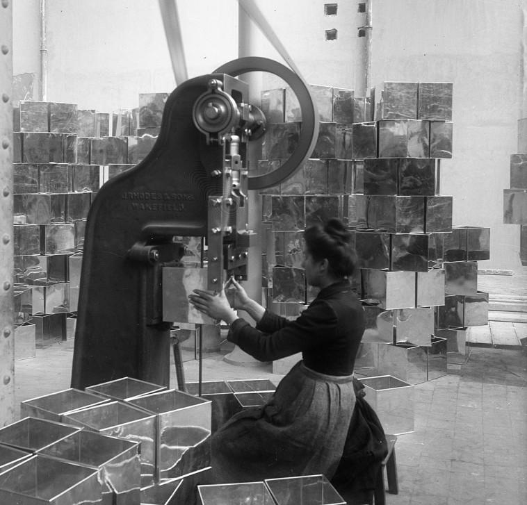 Photographie de femme devant une machine à l'usine